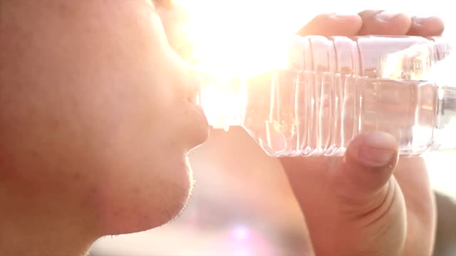 man drinking water silhouette close up