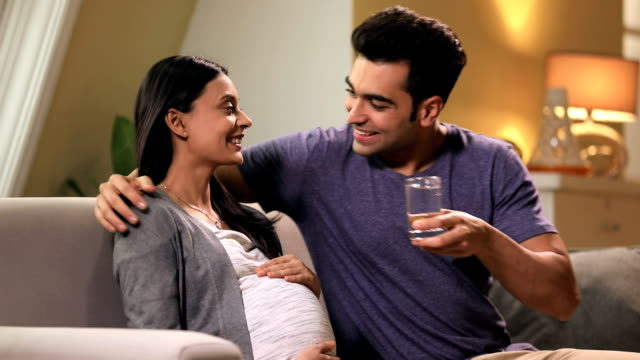 man drinking water to his pregnant wife, delhi, india - drinking glass stock videos & royalty-free footage