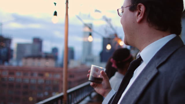 Man Drinking Whisky at Rooftop Party