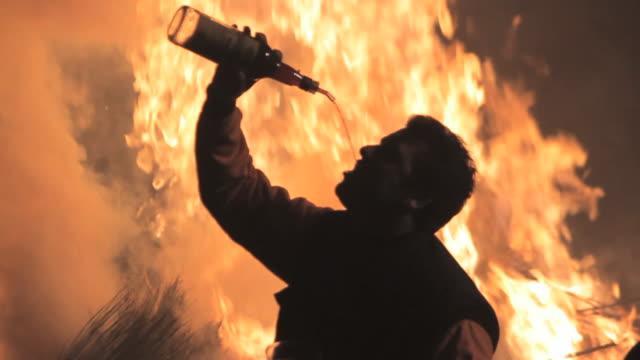 vídeos y material grabado en eventos de stock de m/s man drinking wine silhouetted against a big bonfire - chispas