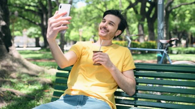 vídeos y material grabado en eventos de stock de man drinking yerba mate en urban park - mate técnica de vídeo