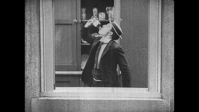 stockvideo's en b-roll-footage met 1921 man (buster keaton) drinks whiskey out of a bottle marked poison with hopes of committing suicide, but inside of dying, he gets drunk - communication problems