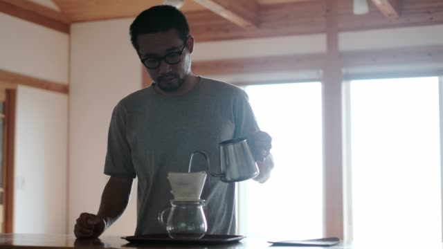 man dripping brewed coffee on kitchen counter - un giorno nella vita video stock e b–roll