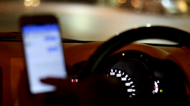 Man driver using smart phone in car at nighttime