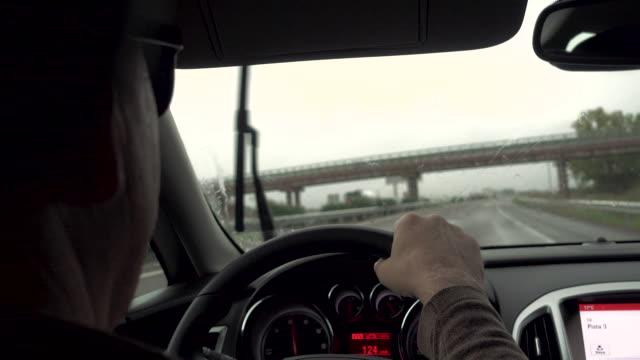 vídeos de stock e filmes b-roll de 4k | man drives a car on a highway in a rainy day - só homens maduros