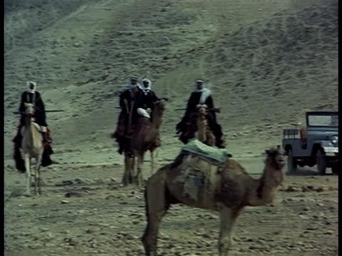 vídeos de stock, filmes e b-roll de a man drives a jeep on a desert road past four men riding camels and carrying rifles. - animal de trabalho