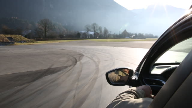 Man drives car at round about, mountains above