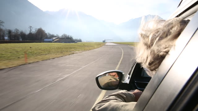 man drives car at round about, mountains above - part of a series stock-videos und b-roll-filmmaterial