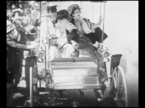 Man drives old car from around the turn of the 20th century as crowd runs alongside car belches smoke in front and veers on road woman in passenger...