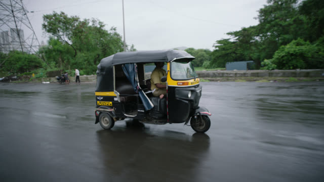 SLO MO. Man drives pedicab down rainy Mumbai street.