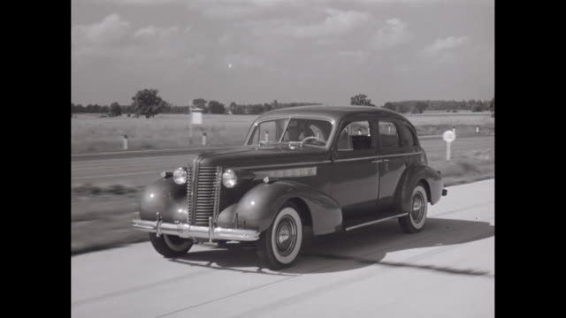 stockvideo's en b-roll-footage met ws ts man driving 1938 buick car on highway / united states - 1930