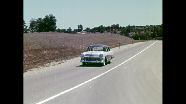 WS PAN Man driving 1957 Chevrolet car on road / United States