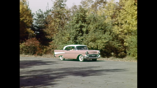 WS TS Man driving 1957 Chevrolet car on road / United States