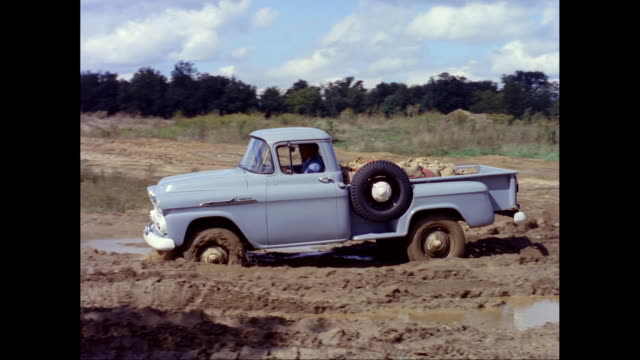 WS TS Man driving 1958 Chevrolet pick-up truck in mud / United States