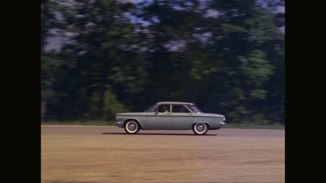 WS TS Man driving 1960 Chevrolet Corvair car on road / United States