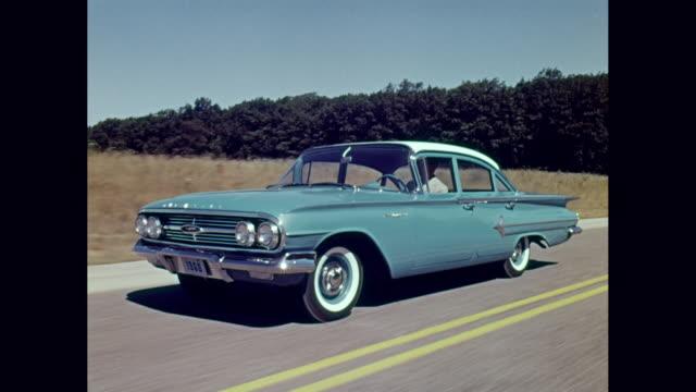 ws pov man driving 1960 chevrolet impala car on road / united states - 1960年点の映像素材/bロール