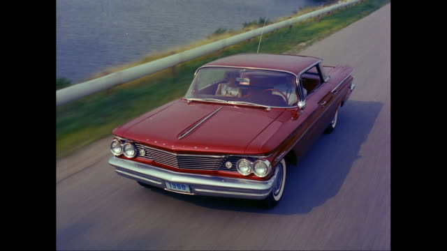 ms ts ha man driving 1960s chevrolet car on road / united states - chevrolet stock videos & royalty-free footage