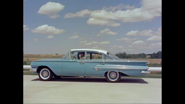 vidéos et rushes de ws ts man driving 1960s chevrolet impala on road / united states - chevrolet