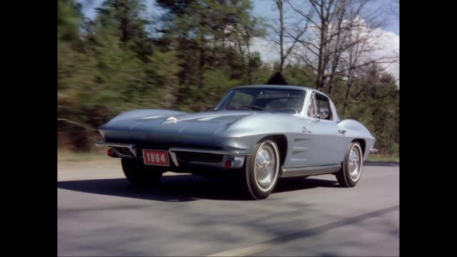 vidéos et rushes de ws ts man driving 1964 chevrolet corvette car moving on street / united states - chevrolet