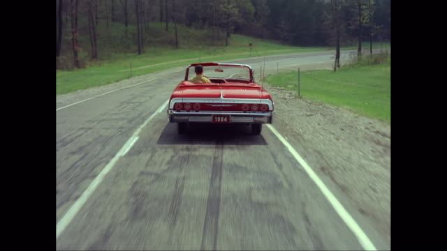 vidéos et rushes de ws pov man driving 1964s car on road / united states - sign
