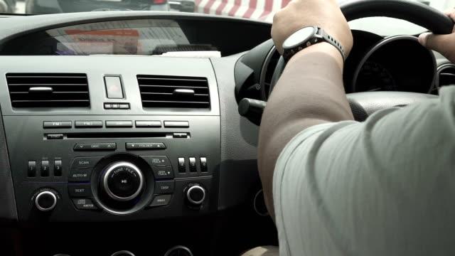 vídeos de stock e filmes b-roll de a man driving a car in the city in daylight. - rádio aparelhagem de áudio
