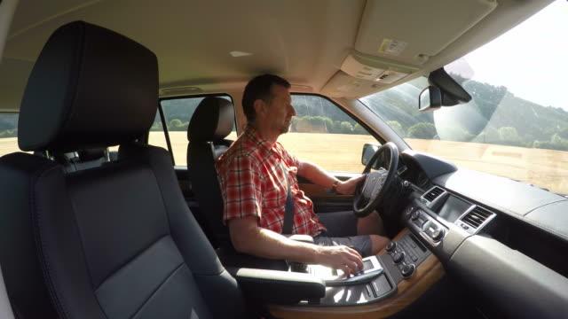 vídeos de stock, filmes e b-roll de man driving a car - camisa pólo
