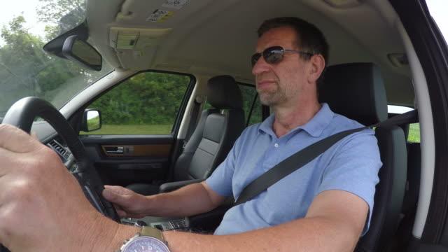 vídeos de stock e filmes b-roll de man driving a car - t shirt