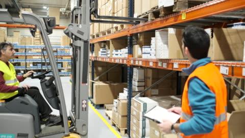 vídeos y material grabado en eventos de stock de hombre conduciendo una carretilla elevadora en un gran almacén industrial. - vehículo terrestre