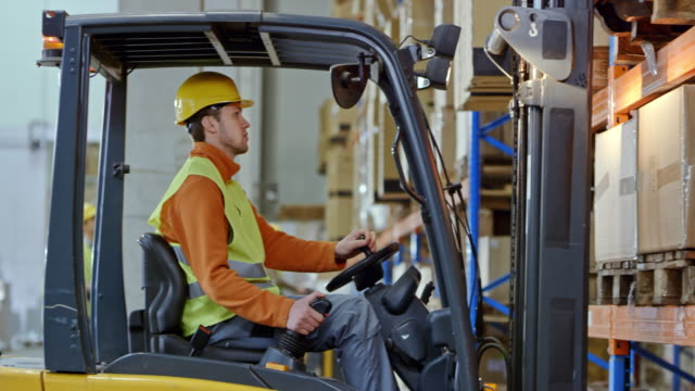 man driving a forklift in the warehouse taking a pallet off the pallet rack - forklift stock videos & royalty-free footage