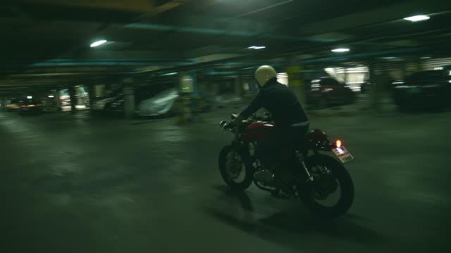 stockvideo's en b-roll-footage met man het besturen van een motorfiets op donkere parkeren - hoofddeksel
