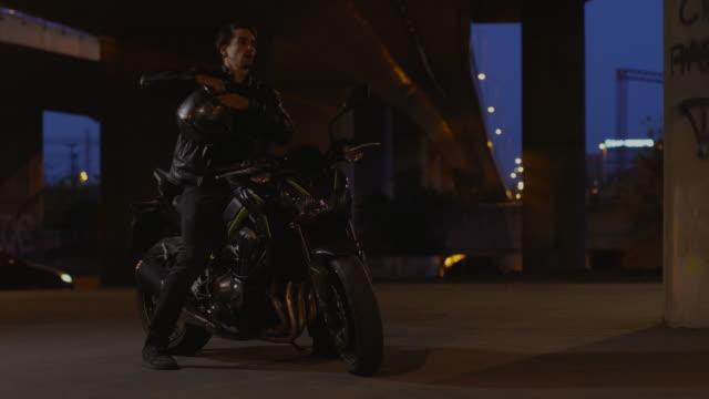 vídeos y material grabado en eventos de stock de hombre conduciendo una moto en la noche - aparcar