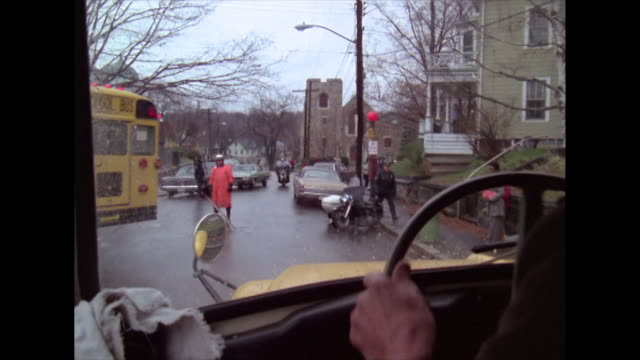 of man driving a school bus in convoy in the middle of the boston desegregation busing crisis in 1974. driver meets police roadblock on streets and... - blickwinkel aufnahme stock-videos und b-roll-filmmaterial