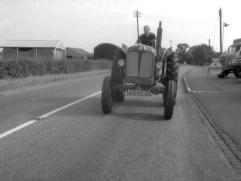 a man driving a tractor stops in front of the camera - 1959 stock-videos und b-roll-filmmaterial