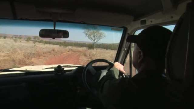 man driving along a dirt road in a desert landscape. editorial use only. - outback stock videos & royalty-free footage