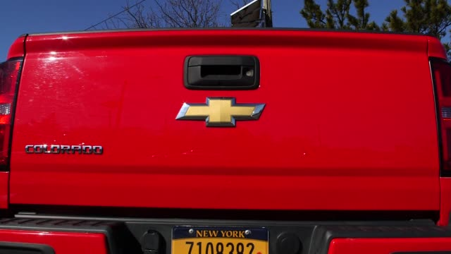 man driving around a red chevrolet truck in a parking lot along a waterfront near new york city, new york on march 12th, 2015 shots close shot of a... - シボレー点の映像素材/bロール