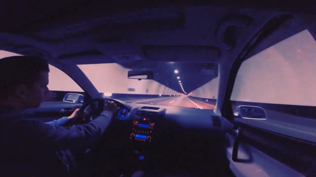 Man driving at night inside a tunnel from inside view.