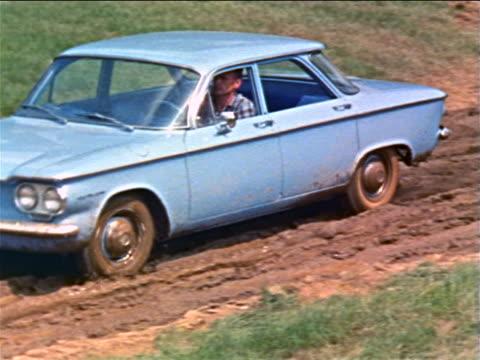 1960 pan man driving blue corvair on muddy road / industrial - シボレー点の映像素材/bロール