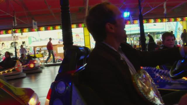 ms shaky, man driving bumper car at oktoberfest fair, munich, germany - bumper car stock videos & royalty-free footage
