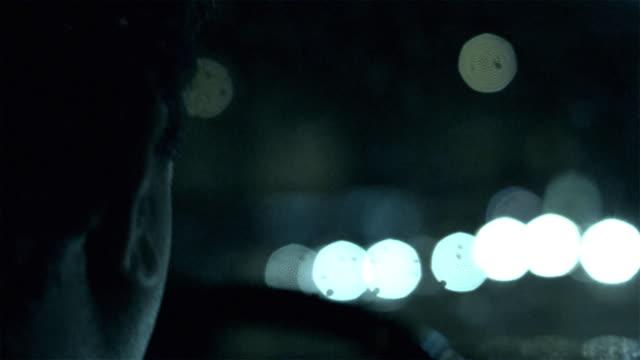 CU POV Man driving car at night / New York City, New York, USA