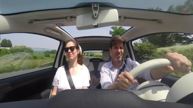 vidéos et rushes de man driving car, pov man driving convertible, with a passaged woman - intérieur de véhicule