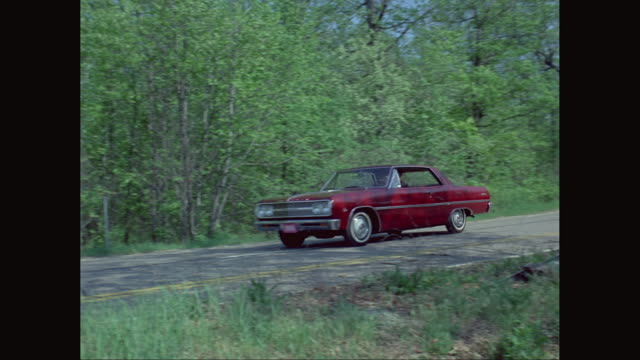 ws pan man driving car on country road / united states - vintage car stock videos and b-roll footage