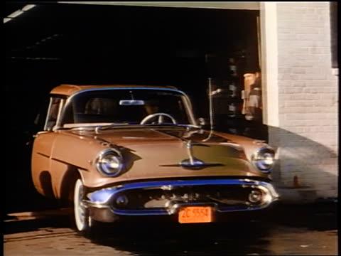 1958 man driving car out of automatic car wash / people start to wipe windshield / newsreel - biltvätt bildbanksvideor och videomaterial från bakom kulisserna