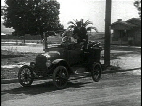 vidéos et rushes de b/w 1924 man driving car quickly causing backseat + keystone kop (will rogers) to fall to ground - 1924