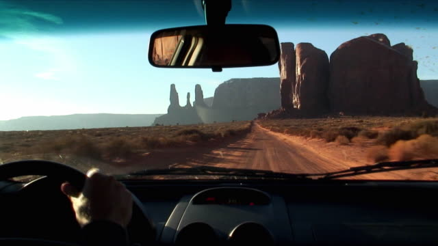 pov man driving car through monument valley, view of three sisters, arizona, usa - car interior stock videos & royalty-free footage
