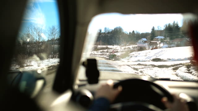 Man driving car through snowcapped country side