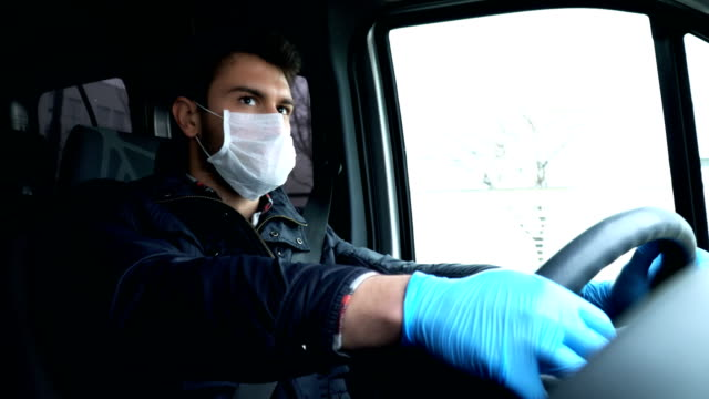 vídeos de stock e filmes b-roll de man driving car with face mask and glove. prevention for coronavirus. - transportation