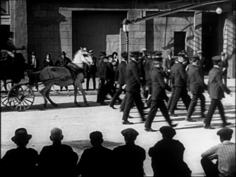 b/w 1922 man driving cart stopping behind police marching in parade / feature - animale da lavoro video stock e b–roll