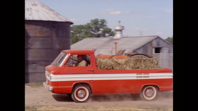 ws pan man driving chevrolet pick-up truck on dirt track past red barn / united states - hay bail stock videos & royalty-free footage