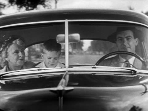 B/W 1952 man driving Chevrolet (Fleetline?) with young boy + senior woman  passengers