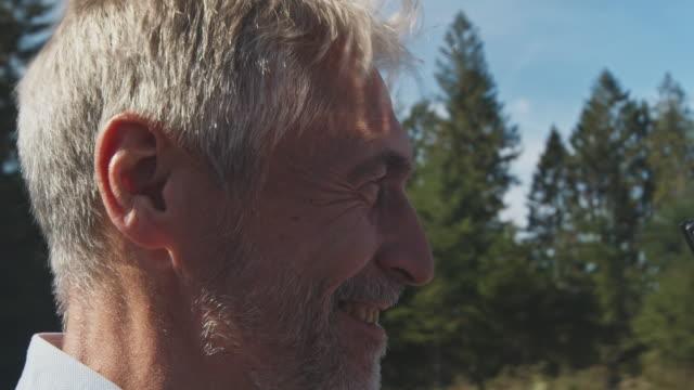 vídeos de stock e filmes b-roll de man driving classic car in summer - cabelo grisalho